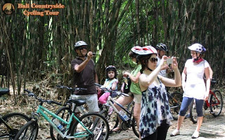 One family Riding Bike with kid and baby in bamboo forest with safety in Ubud